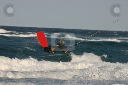 Jumper stock photo, A kite surfer in a black wetsuit jumping clear above the waves on a red board by Ian Genis