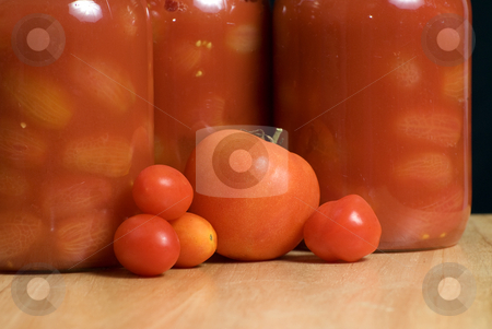 Mason Jars of Tomatoes stock photo, Mason jars full of canned tomatoes shot on a wooden cutting board by Richard Nelson