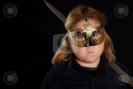 Child Fighter stock photo, Closeup view of a young warrior princess holding her sword, shot against a black background with copyspace on the left by Richard Nelson