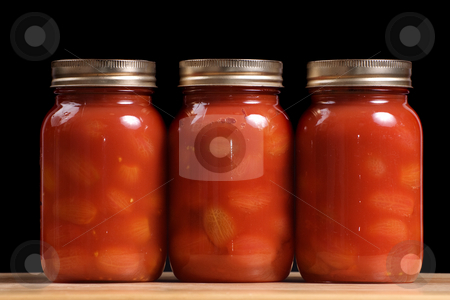 Jars of Tomatoes stock photo, Three jars of canned tomatoes lined in a row by Richard Nelson