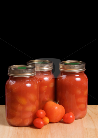 Canned Tomatoes stock photo, Three mason jars filled with canned tomatoes shot on a wooden board and isolated against a black background by Richard Nelson