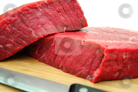 Fresh Raw Steak stock photo, A large uncooked steak on a cutting board with butcher knife on a white background by Lynn Bendickson