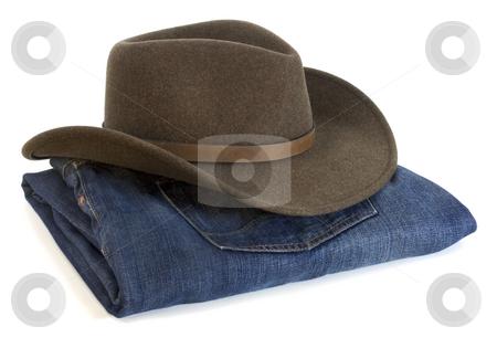 Cowboy hat and blue jeans stock photo, Felt wool brown (olive) cowboy hat and blue folded jeans on white background by Marek Uliasz