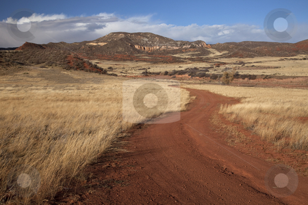 Windy ranch road in mountain valley stock photo, Windy road in Red Mountain Open Space in northern Colorado (Larimer County), fall scenery with dry grass moved by wind by Marek Uliasz