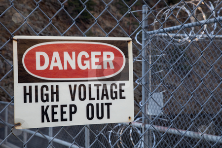 Danger, high voltage, keep out sign stock photo, Danger, high voltage, keep out -  warning sign on a chain link fence with barbed wire on top protecting hydro power plant by Marek Uliasz