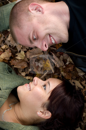 Young Couple In Love stock photo, A young happy couple gazing into each others eyes while laying in a pile of leaves. by Todd Arena