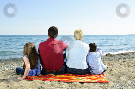 Family sitting at beach stock photo, Family sitting on towel at sandy beach by Elena Elisseeva