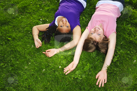 Girl friends stock photo, Two teenage girls laying on grass arms outstretched by Elena Elisseeva
