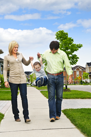 Happy family stock photo, Young happy family playing with son on sidewalk by Elena Elisseeva
