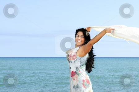 Beautiful young woman at beach stock photo, Portrait of beautiful smiling brunette girl at beach with arms outstretched by Elena Elisseeva
