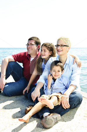 Happy family stock photo, Happy family sitting on pier at lake by Elena Elisseeva