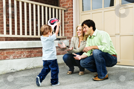 Family playing with soccer ball stock photo, Happy young family playing soccer with toddler on driveway by Elena Elisseeva