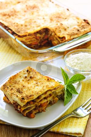 Lasagna stock photo, Fresh baked lasagna casserole with a serving cut by Elena Elisseeva