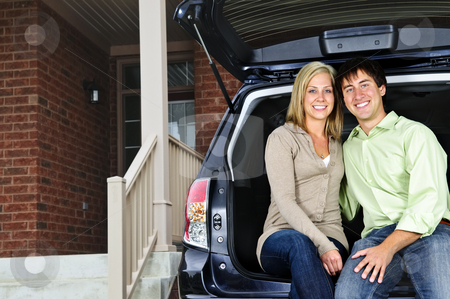 Couple sitting in back of car stock photo, Happy young couple sitting at back of car on driveway by Elena Elisseeva