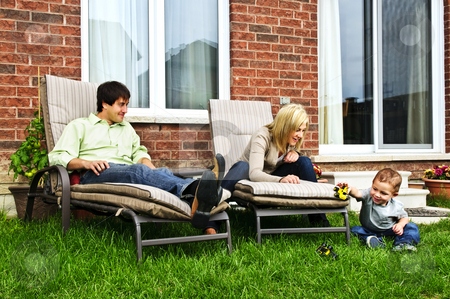 Happy family relaxing at home stock photo, Happy family relaxing in backyard of new home with toddler by Elena Elisseeva