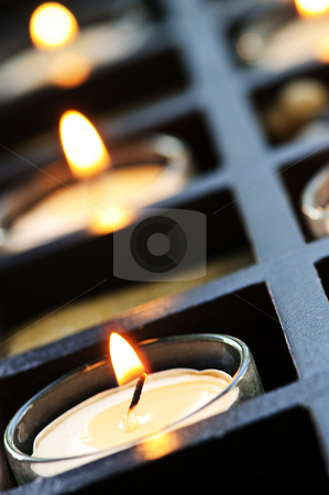 Candles stock photo, Burning candles in glass holders and wooden stand by Elena Elisseeva