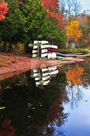 Fall forest reflections with canoes stock photo, Canoes at forest of colorful autumn trees reflecting in calm lake by Elena Elisseeva