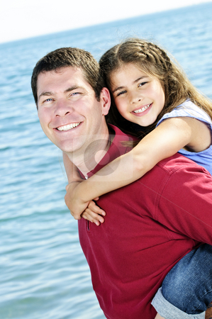 Father and daughter stock photo, Portrait of father giving piggyback ride to daughter at seashore by Elena Elisseeva