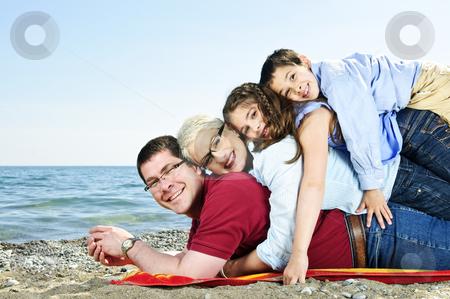 Happy family at beach stock photo, Portrait of a happy family having fun on a beach by Elena Elisseeva
