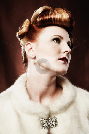 Woman Looking Up and Away stock photo, A woman is wearing a fur coat and a brooch, and is looking up and away from the camera.  Vertically framed shot. by Media Deva