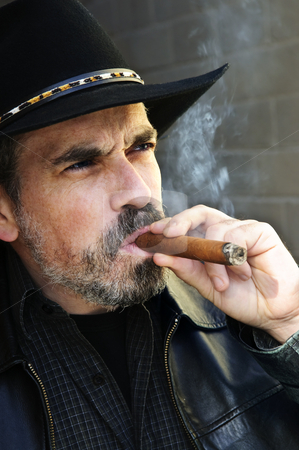 Bearded man smoking cigar stock photo, Man with beard in cowboy hat smoking cigar by Elena Elisseeva