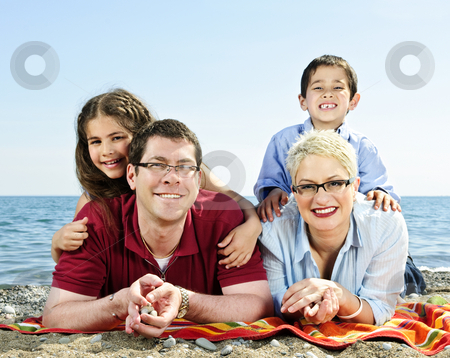 Happy family at beach stock photo, Happy family laying on towel at sandy beach by Elena Elisseeva