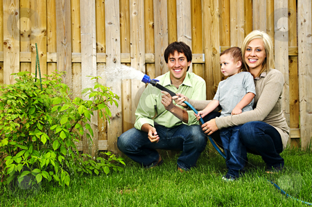 Family watering plant stock photo, Happy family in backyard watering plant with hose by Elena Elisseeva