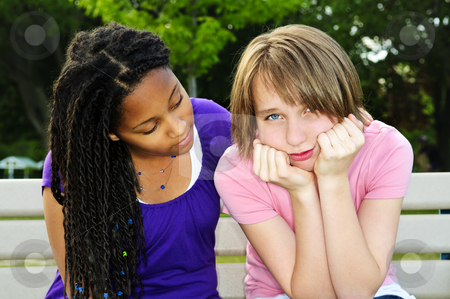 Teenager consoling her friend stock photo, Teenage girl consoling her sad upset friend by Elena Elisseeva