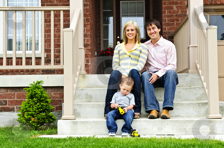 Happy family at home stock photo, Young family sitting on front steps of house by Elena Elisseeva