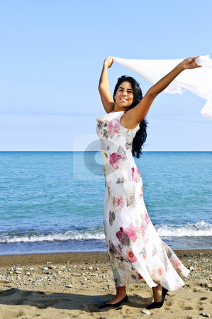 Beautiful young woman at beach with white scarf stock photo, Portrait of beautiful smiling brunette girl at beach holding white scarf by Elena Elisseeva