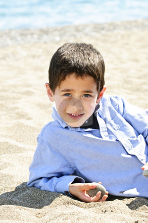 Young boy at beach stock photo, Portrait of young boy laying on sand at the beach by Elena Elisseeva