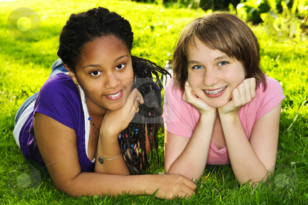 Girl friends stock photo, Two happy teenage girls laying on grass by Elena Elisseeva