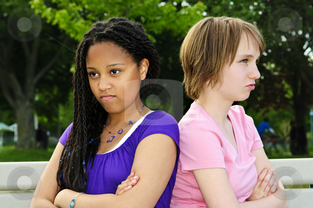 Angry teenage girls stock photo, Two unhappy teenage girls sitting on bench by Elena Elisseeva