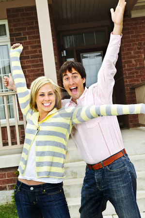 Excited couple at home stock photo, Young excited couple celebrating in front of home by Elena Elisseeva