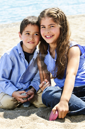 Brother and sister at beach stock photo, Portrait of brother and sister sitting on sand at the beach by Elena Elisseeva