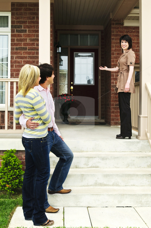 Happy couple with real estate agent stock photo, Real estate agent with couple welcoming to new home by Elena Elisseeva