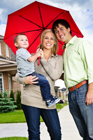 Happy family with umbrella stock photo, Young happy family under umbrella on sidewalk by Elena Elisseeva
