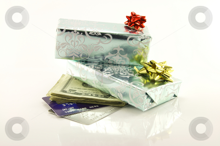 Gifts with Money and Credit Cards stock photo, Two shiny silver gifts with a gold and red bows, dollars and plastic credit cards on a reflective white background by Keith Wilson