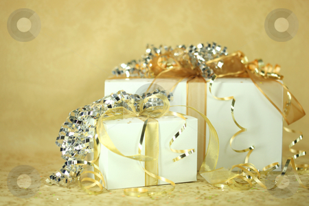 Presents stock photo, Closeup of two presents wrapped in gold and silver. No one is viewable in the image. Horizontally framed shot. by Katrina Brown