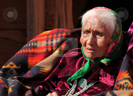 Elderly Native American Woman stock photo, An elderly Native American woman sits among blankets. She is head and shoulders viewable and looking away from the camera. Horizontally framed shot. by Katrina Brown