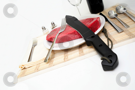 Big Steak - Big Knife stock photo, A large raw beef steak served on a white plate with silverware and a large black knife by Lynn Bendickson