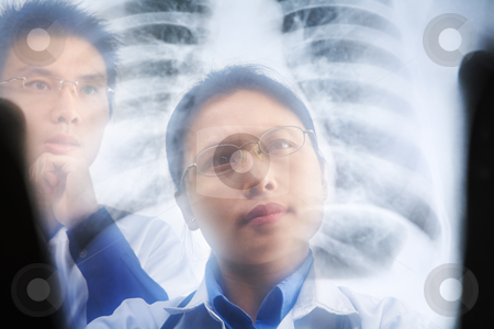 Two Asian doctor examining xray result stock photo, Two Asian doctor examining xray result. PS:the image taken from behind the xray print, so it may leave some soft noise on the people image behind it. by Rudyanto Wijaya