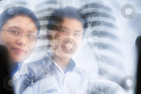 Two Asian doctor smiling through the xray result stock photo, Two Asian doctor smiling through the xray result. PS:the image taken from behind the xray print, so it may leave some soft noise on the people image behind it. by Rudyanto Wijaya
