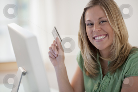 Young Woman Shopping Online stock photo, Young woman sitting in front of a computer with a credit card and smiling at the camera. Horizontal format. by Edward Bock