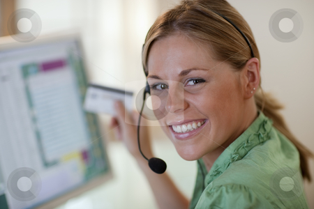 Young Woman With Headset and Credit Card stock photo, Close-up of a smiling young woman in front of a computer, wearing a headset and holding a credit card. Horizontal format. by Edward Bock