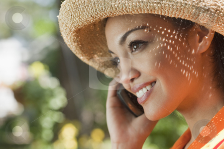 Smiling Young Woman With Cell Phone stock photo, Close-up side view of a smiling young woman using a cell phone in an outdoor setting. Horizontal format. by Edward Bock