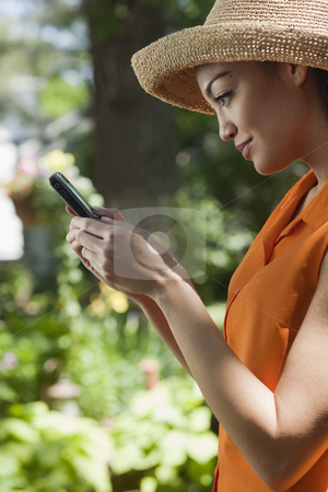 Young Woman With Cell Phone in Garden stock photo, Profile of a young woman standing in a garden and looking at her cell phone. Vertical format. by Edward Bock