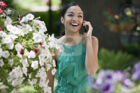 Young Woman in Garden With Cell Phone stock photo, A young woman smiles while talking on her cell phone in a garden. Horizontal format. by Edward Bock