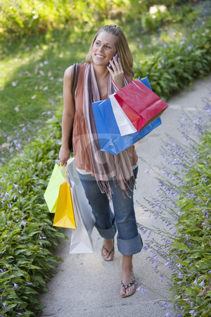 Young Woman with Shopping Bags and Cell Phone stock photo, High angle view of a woman holding shopping bags and using a cell phone. Vertical format. by Edward Bock