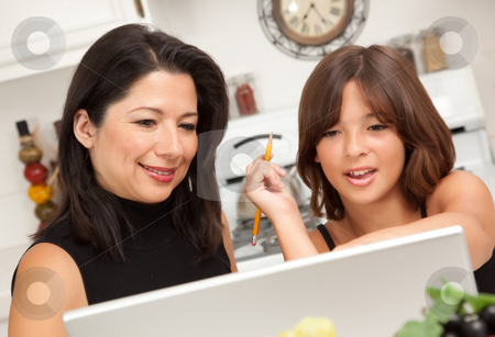 Attractive Hispanic Mother & Daughter on the Laptop stock photo, Attractive Hispanic Mother & Daughter in the Kitchen using the Laptop. by Andy Dean